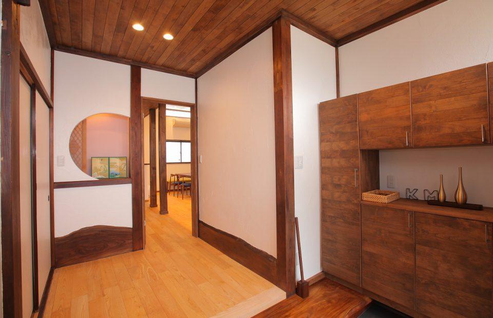 既存のけやきの巾木を生かし、床・天井には無垢材、壁は漆喰の真壁づくり、木の温もりを感じる玄関に
