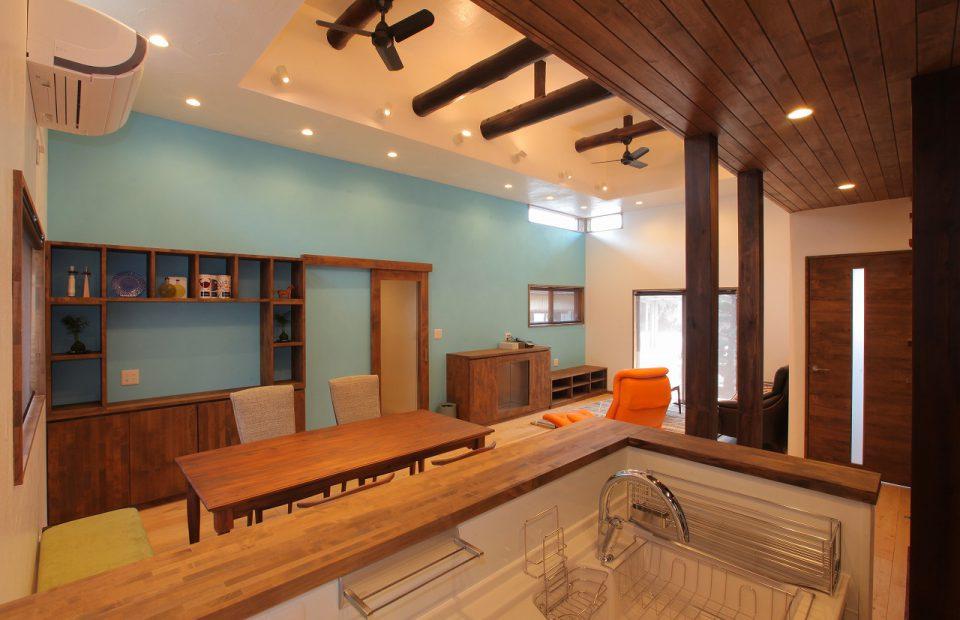 LDKは壁際に無垢のオリジナル造作家具と暖炉を配して温もりを感じる空間に。壁面の一部はポーターズペイントで塗装し、明るすぎない水色がモダンな雰囲気