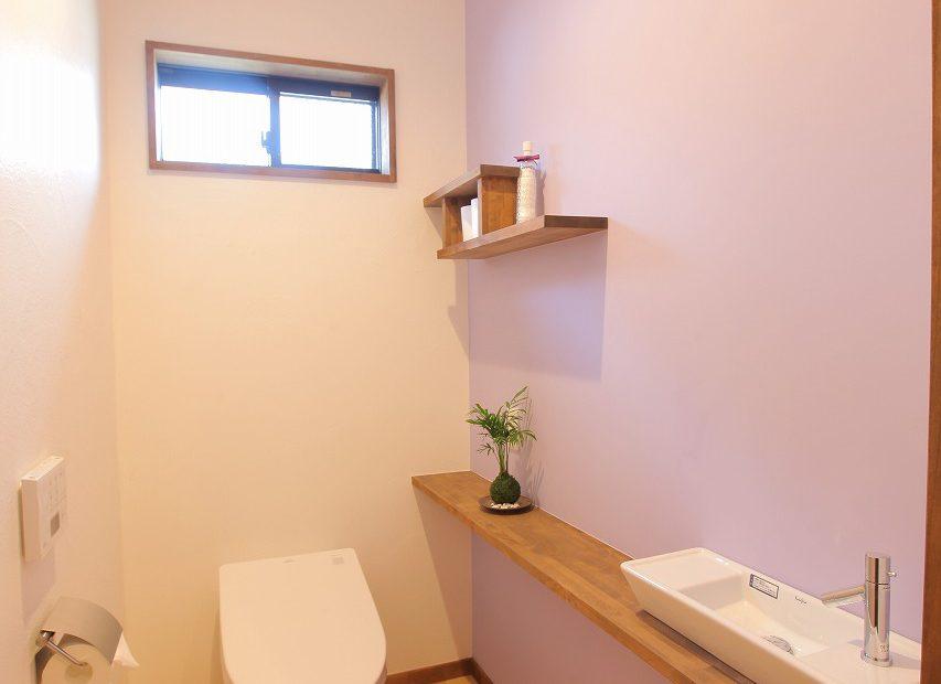 広めのトイレには手洗いカウンターを造り付け、壁面に鮮やかな薄紫を塗り、さわやかな印象に
