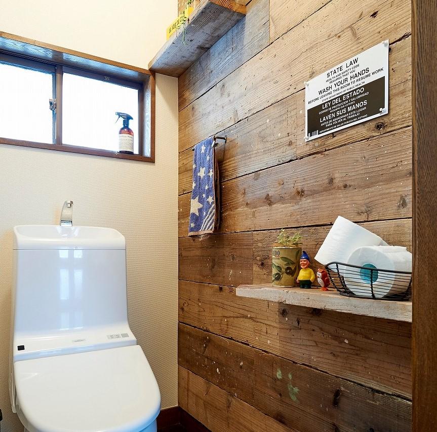トイレの壁一面にも古材を貼ってセンスよく。シンプルな飾り棚がおしゃれな空間です。