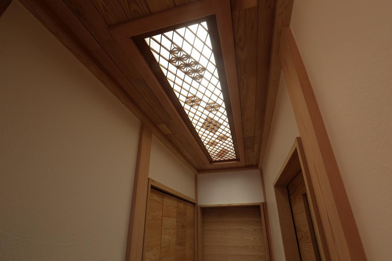 廊下の天井には、かつての付け書院の扉や欄間を活かして照明を演出。和の趣を感じさせます