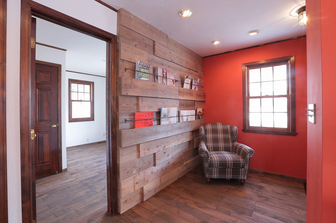 玄関を入ると壁面に古材の板を貼ったライブラリーがお出迎え。ヴィンテージソファで楽しむ読書時間
