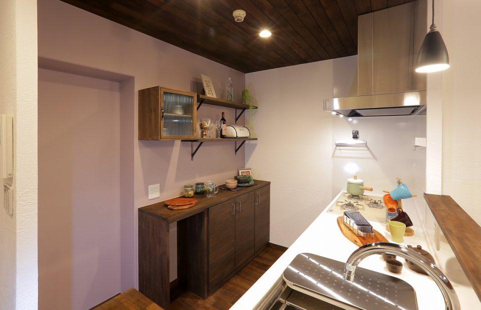 キッチンのカップボードはオリジナルを造作。収納の手前の空間には、購入を決めていたゴミ箱がぴったり収まるサイズに。アクセントカラーの壁でよりおしゃれな空間に仕上がりました