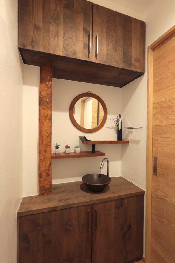 トイレの手洗い場にはかつての床の間の柱や段違い棚を活かし、和の趣に合わせて無垢材の造作収納と陶製の水鉢を使っています
