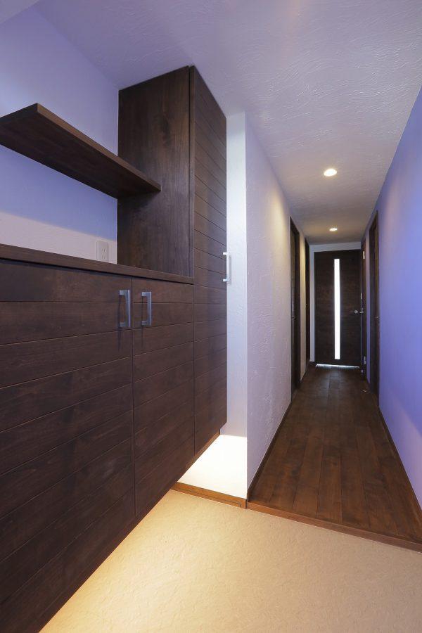 玄関からリビングに続く廊下の壁一面はラベンダ―カラーに塗装。玄関収納はフロートタイプにして間接照明で演出