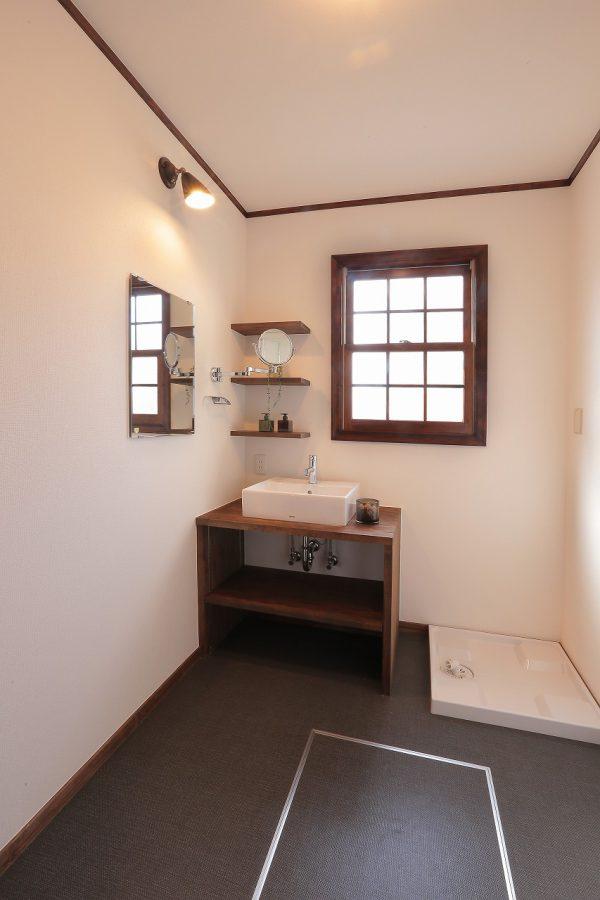無垢材で作ったかわいらしい洗面台。壁面に取り付けた拡大鏡や飾り棚でホテルライクな暮らしを