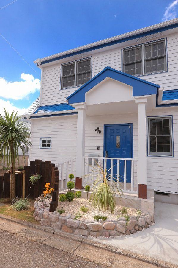 白地にビビッドなブルーの玄関ドアが映えます。US風のポストもアクセントに
