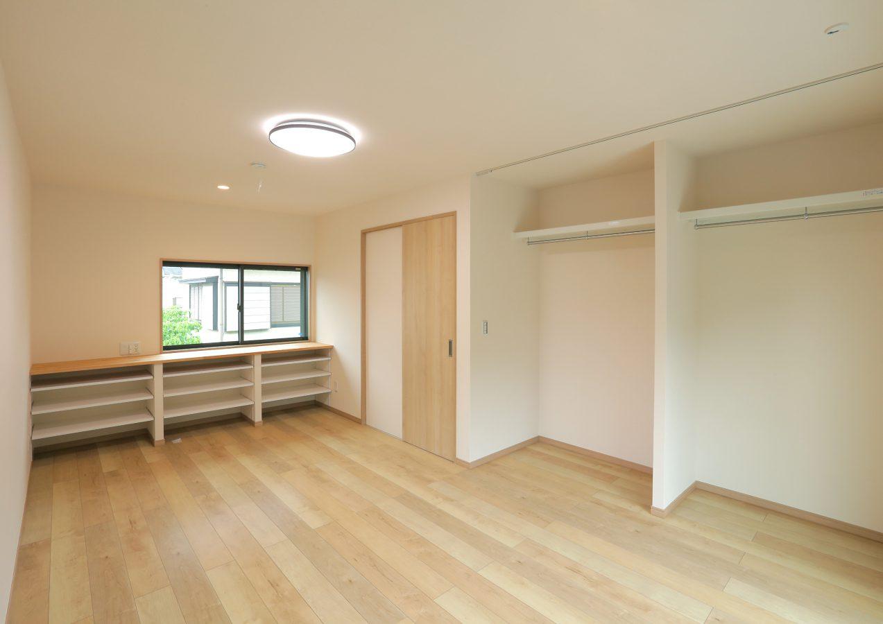 扉をなくしたオープンなクローゼットで広々とした主寝室。造作カウンター収納は可動棚を取れば、机としても使用できます