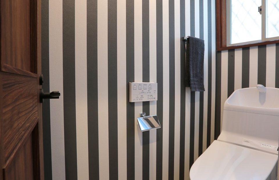 ストライプの壁で仕上げたトイレ。ラスティックな木扉ともとても良い相性。