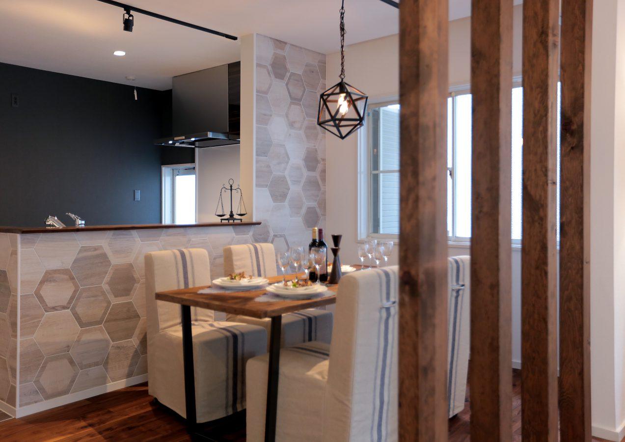 温かみのある木のパーテーションがアクセントのダイニング。キッチン奥の壁はモダンなヘキサゴンタイル。