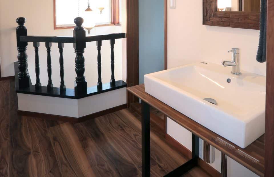 2階の洗面台にはアイアン黒革仕上げの足をつけ、さりげなくインダストリアル感を演出。階段手摺との相性も◎