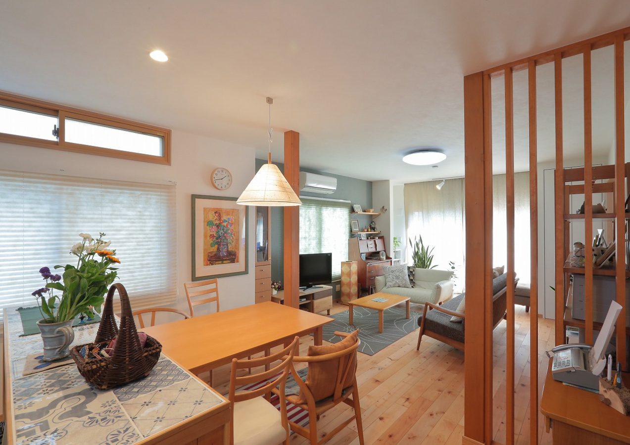 既存のダイニングキッチンと和室をLDKに変更。構造の柱は木格子と合わせてアクセントに。