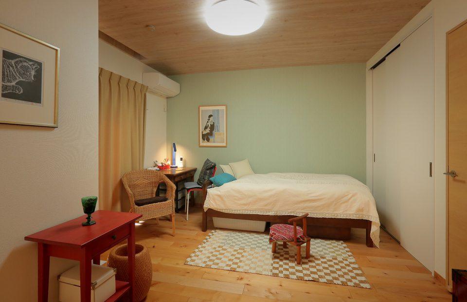 寝室の壁はアクセントクロスで薄いグリーンに、天井は木目クロスで北欧風に。