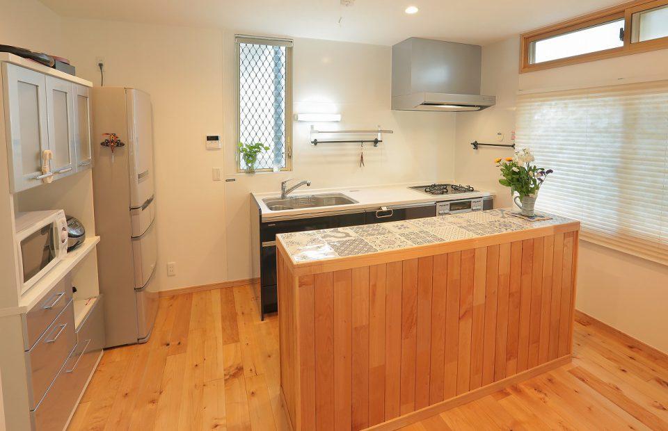 キッチンは対面カウンターで見せたくないものは隠し、天板はクラシカルな模様のタイルで仕上げました。