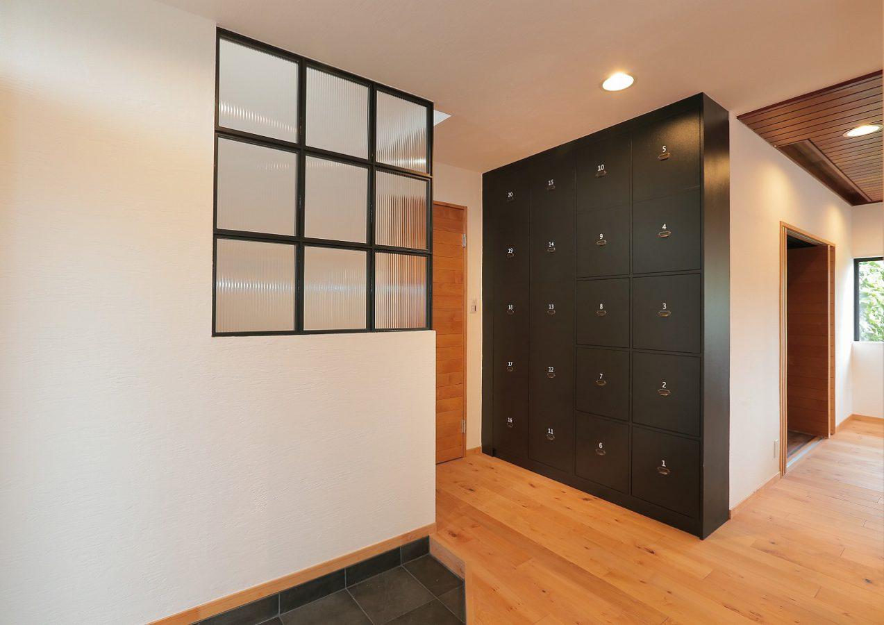 玄関を開けたとたんに広がる開放的な居住空間。ホール側面に設けたアイアンのガラスパーテーションからは、吹き抜け階段の窓から差し込む暖かい光をほのかに感じる事ができます。正面壁にはインテリアのアクセントにもなる大容量のヴィンテージ調ロッカー式収納がお目見え。