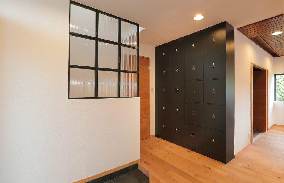 玄関を開けたとたんに広がる、開放的なファミリーの居住空間。ホール側面に設けたアイアンのガラスパーテーションからは、向こう側、吹き抜け階段の窓から差し込む暖かい光を、ほのかに感じる事ができます。正面壁には、インテリアのアクセントにもなる、大容量のヴィンテージ調ロッカー式収納。