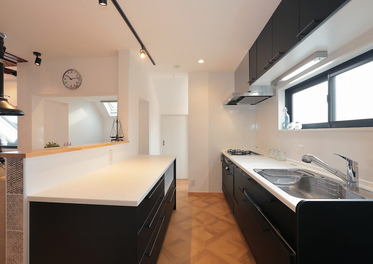 特注黒革仕上げのシャープなキッチン。お料理上手なお施主様のために「オトコの台所」仕様となりました。床は使い勝手を考慮して、パーケトリー柄のフロアタイルを敷き詰めて。LD側の無垢のメープルフローリングとも相性も◎