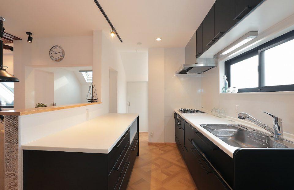 特注黒革仕上げのシャープなキッチン。お料理上手な施主仕様ーやや「オトコの台所」仕様となりました。床は使い勝手を考慮して、LD側の無垢のメープルフローリングとも相性よし、パーケトリー柄のフロアタイルを敷き詰めて