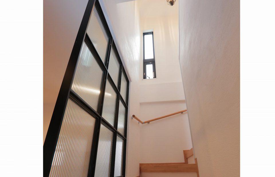 アイアンのガラスパーテーションで仕切られた階段を上ってゆく。施主セレクトのペンダントランプの柔らかい光が、階段室の漆喰壁に、エレガントに反射します。