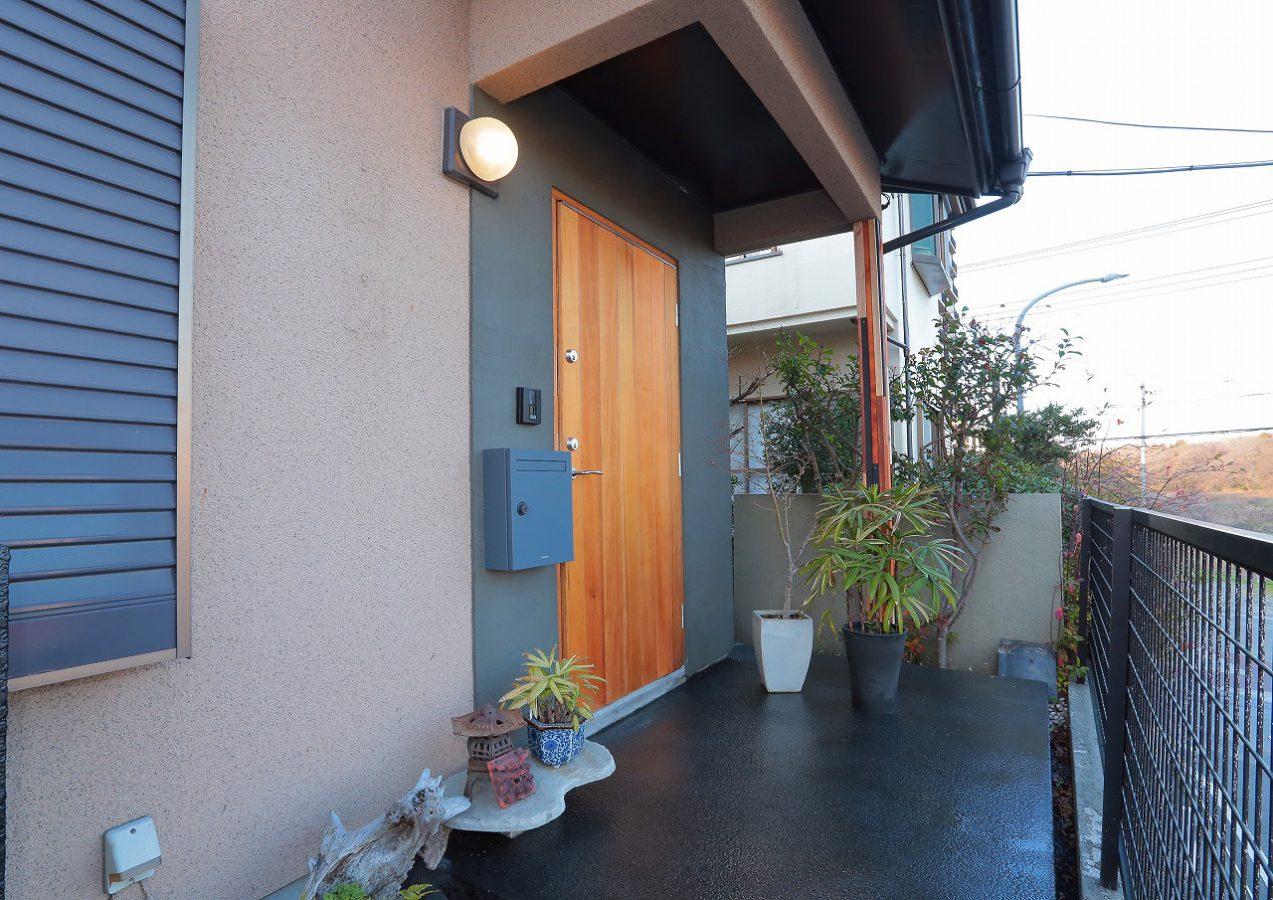 木製の玄関ドアを採用しモルタル壁のアクセント。床は洗い出し仕上で和の設えです