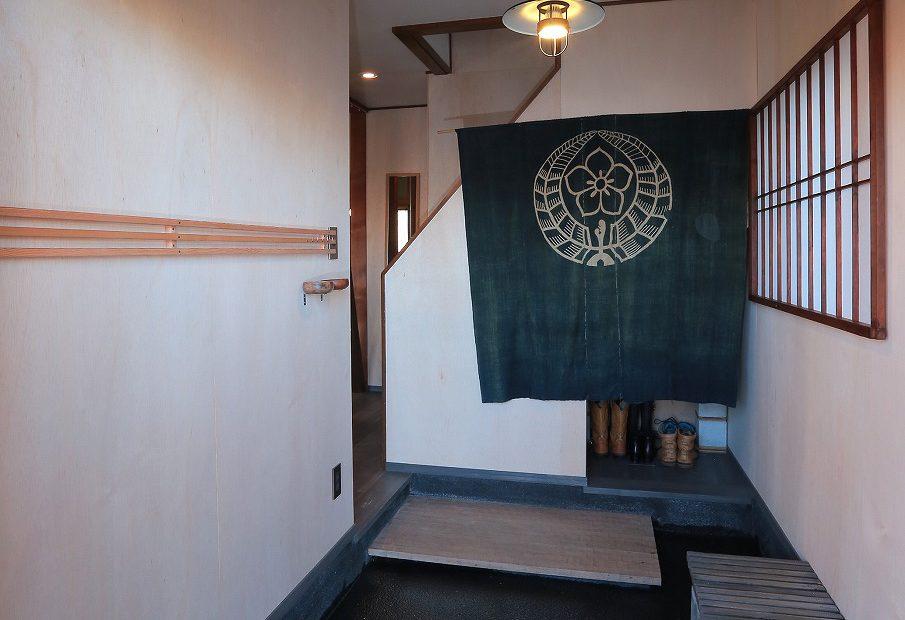 洗い出しの床に名栗加工した無垢オーク材の式台を採用した玄関。障子と暖簾で旅館のような設えに