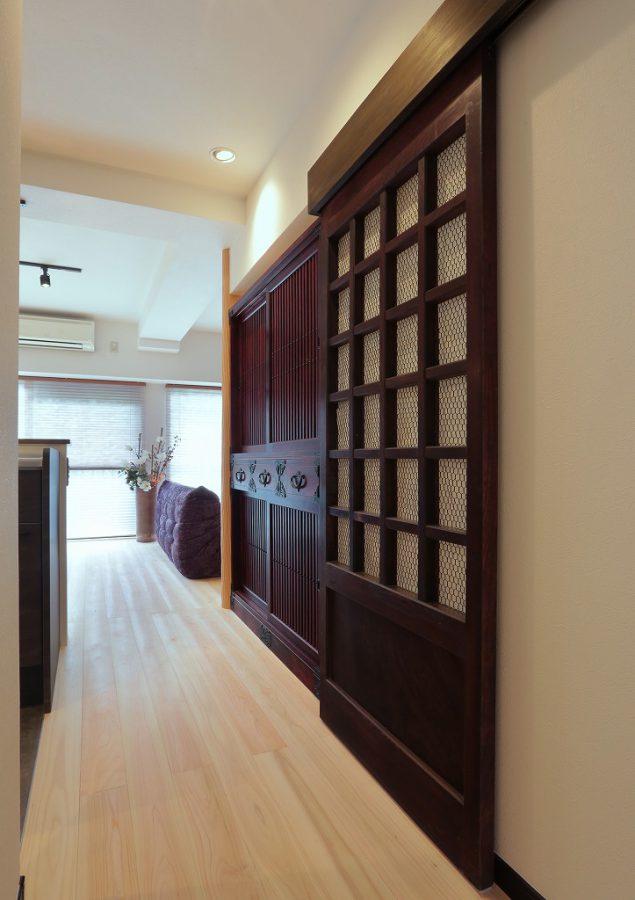 古民家から出土した蔵戸を和室の出入り口へ設置。現代の建具よりサイズが小さいため、お品に合わせて造り込みました。奥には岩屋堂水屋箪笥が。いずれも奥様がこの時のために厳選された品々ばかりです