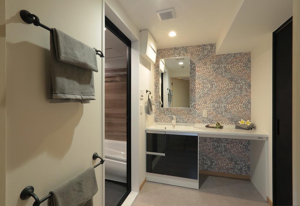 ホテルライクをイメージした水回り空間はシックな色で統一することで、正面の大胆な柄の壁紙が一層際立ちます。