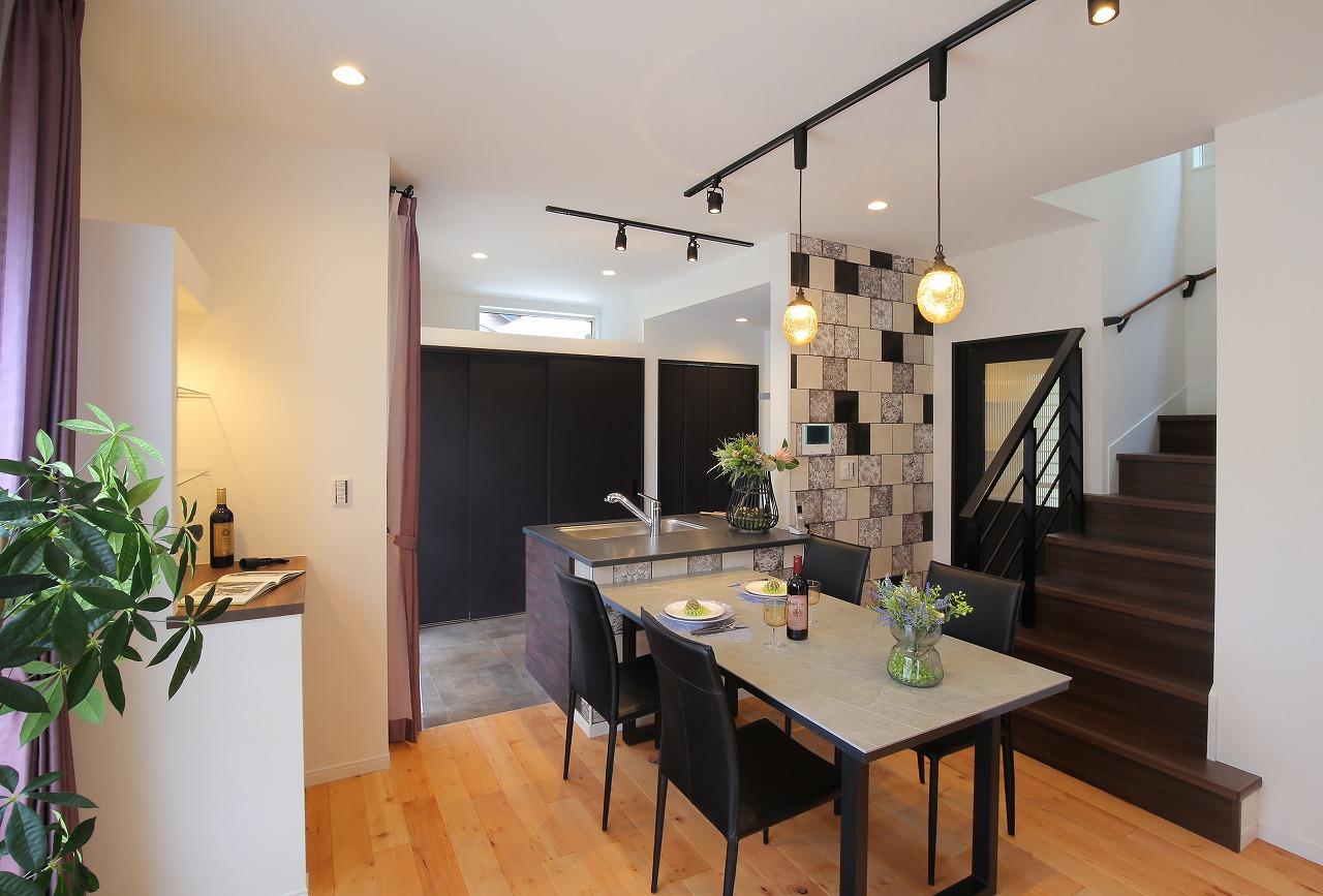 イタリア製のタイルで飾ったダイニング。照明や家具、キッチンの天板をブラックで統一したことで高級感漂う特別な空間になりました。