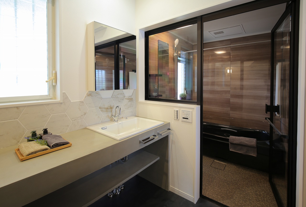 タイルが施された洗面は広々ゆったり。透明ガラスで見える浴室と相まってまるで上質なホテルのよう。
