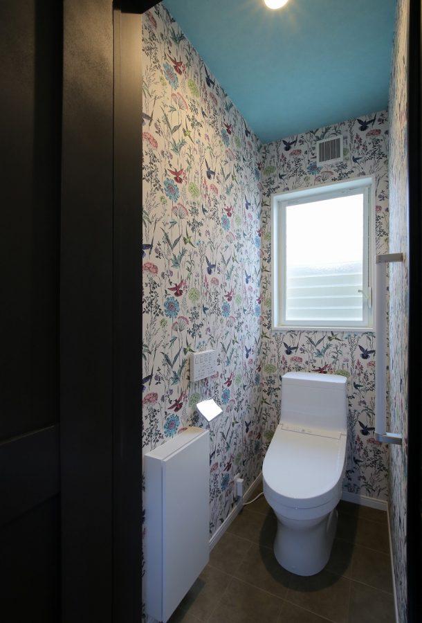 天井のスカイブルーの壁紙は、花柄模様の一部と合わせて統一感のある色合いに。狭い空間だからこそ遊び心が発揮できるトイレならではのデザインです。